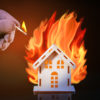 Hand in glove with a burning match sets fire to the house model of matches, risk, property Insurance.  House And Fire. Playing With Fire.