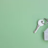 White key with a keychain in the form of a house on a light green background. The concept of buying, selling, renting real estate, mortgages, your own home. Place for text